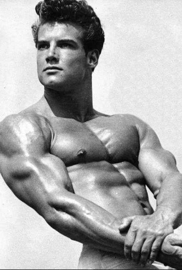 Photo of the bodybuilder Steve Reeves, showing his fully developed chest from doing the bench press.