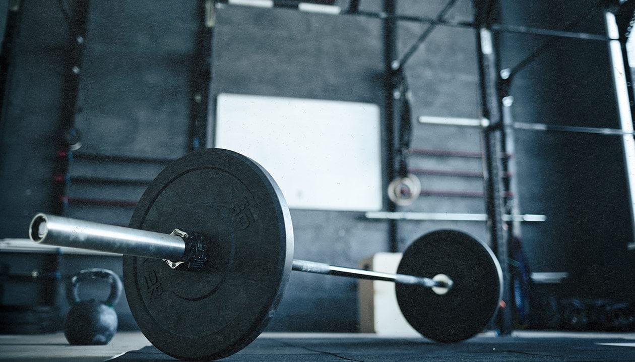 Imagen de una barra de levantamiento en el suelo con un disco a cada lado